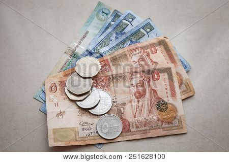 Jordanian Dinars Banknotes And Piastres Coins Lay On Gray Paper Background, Close-up Photo