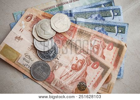 Jordanian Dinars And Piastres Lay On Gray Paper Background, Close-up Photo