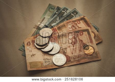 Jordanian Dinars And Piastres Lay On Gray Paper Background, Close-up Vintage Stylized Photo With Ton
