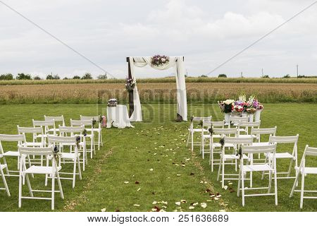 Beautiful Wedding Ceremony On A Field With White Chairs. Place For Wedding Ceremony With Wedding Arc