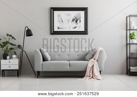 Industrial Black Floor Lamp And A Pink Blanket On An Elegant Settee With Cushions In A Gray Living R