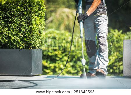 Patio Pressure Cleaning. Caucasian Men Washing His Concrete Floor Patio Using High Pressured Water C
