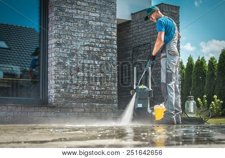 Pressure Washer Cleaning In Front Of The House. Caucasian Men In His 30s Washing Concrete Bricks Dri