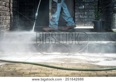 Pressure Washer Cleaning Time. Men Cleaning Outside House Stairs With Power High Pressured Cleaner.