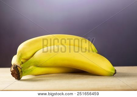Group Of Five Whole Fresh Yellow Banana One Ripe Cluster With Grey Gradient Behind
