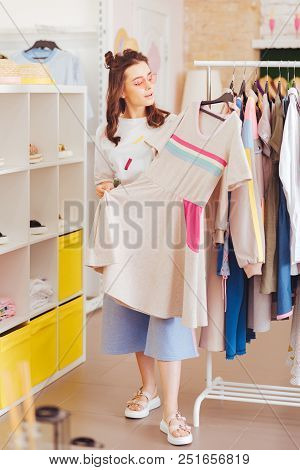 Clothes Rack. Famous Prosperous Fashion Blogger Standing Near Clothes Rack In New Showroom Choosing