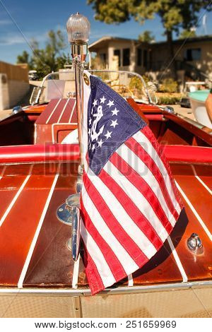 Classic Wooden Speed Boat With Nautical Flag Docked In Front Of A House On The Lake - View From Back