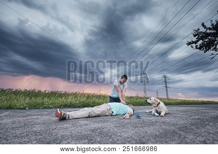 Resuscitation On The Rural Road Against Storm. Loyal Dog (labrador Retriever) Waiting Near His Owner