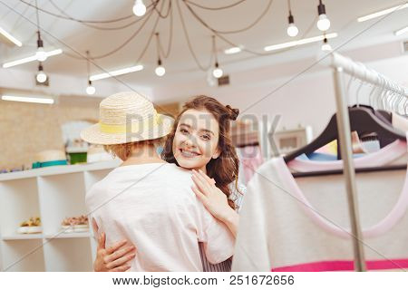Joining Mother. Dark-haired Daughter Smiling Broadly While Joining Her Mother In Shopping Mall