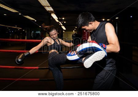Girl Doing Kick Exercise During Kickboxing Training With Personal Trainer