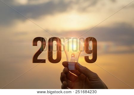 2019 Ideas Concepts With Hand Holding Light Bulb In The Sky.