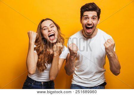 Portrait of positive beautiful man and woman in basic clothing screaming and clenching fists like winners or happy people isolated over yellow background