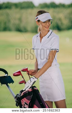 Portrait Of Smiling Female Golf Player In Cap With Golf Gear At Golf Course