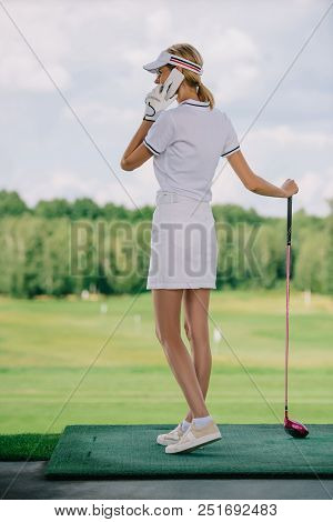 Side View Of Female Golf Player In Polo And Cap With Golf Club In Hand Talking On Smartphone At Golf