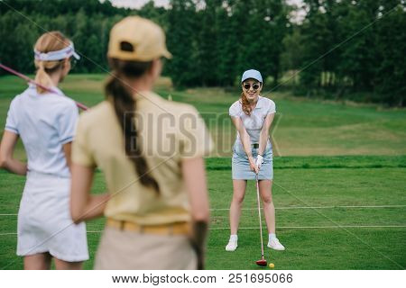 Selective Focus Of Women In Caps With Golf Equipment Looking At Friend Playing Golf At Golf Course