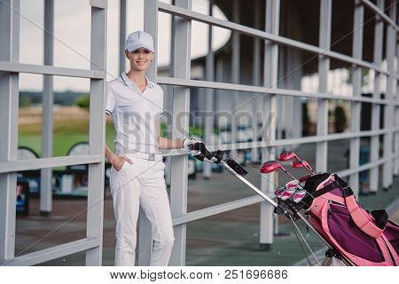 Smiling Female Golf Player In While Polo And Cap With Golf Equipment At Golf Course