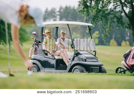 Selective Focus Of Woman Playing Golf While Friends Riding Golf Cart At Golf Course
