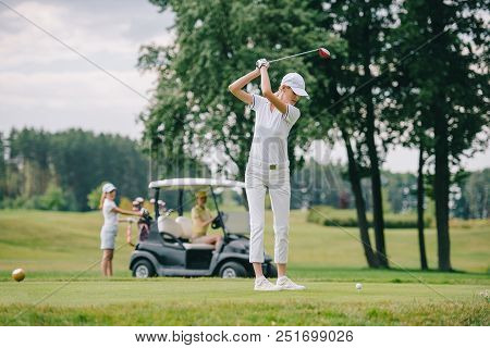 Selective Focus Of Woman With Golf Club Playing Golf And Friends Resting At Golf Cart On Green Lawn
