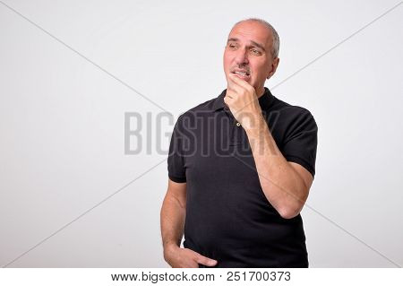 Mature Hispanic Man Thinking With Hands On Chin Looking Away. Close Up Portrait Of Real People. Conc