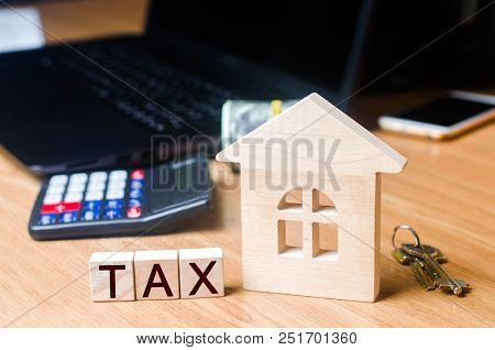 Small Wooden House And Taxes On The Desktop .. Taxes On Real Estate, Payment. Penalty, Arrears. Regi
