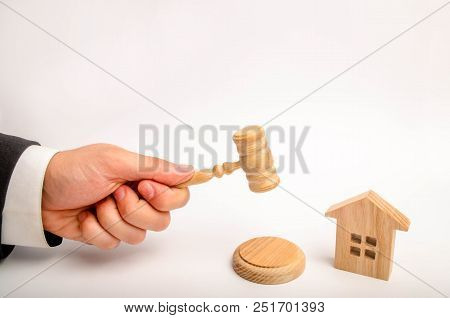 The Judge's Hand Is Holding A Hammer Next To The Wooden House. Trial Of Real Estate. Elimination And