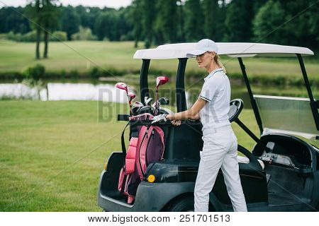 Woman In Polo And Cap With Golf Gear Standing At Golf Cart At Golf Course On Summer Day