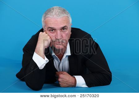 A mature bored businessman laying on the floor. poster