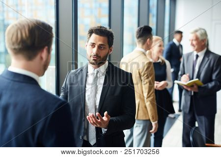 Confident handsome mixed race businessman with beard sharing his opinion with forum participants and gesturing hands during conference break