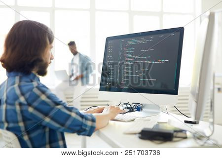 Serious busy hipster young web developer typing on computer keyboard while coding information in modern office