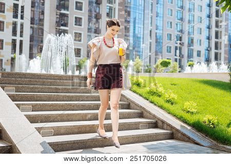Pleasant walk. Attractive young woman walking down the stairs while holding a bottle of juice poster