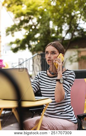 Calling Partner. Young Prosperous Businesswoman Calling Her Partner Waiting For Him In Cafe