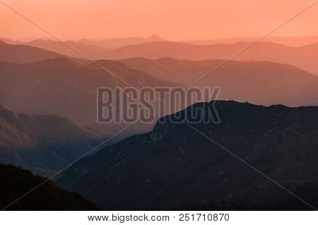 Sunset Over Mountain Ranges Of Sierra Nevada In California. Beautiful Silhouette With Multiple Ridge