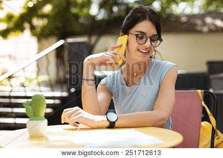 Calling Partner. Smiling Businesswoman Wearing Glasses Calling Her Partner Waiting For Him In Restau
