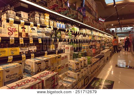 Customer Shopping For Various Selection Of Beer Bottles On Display At Supermarket