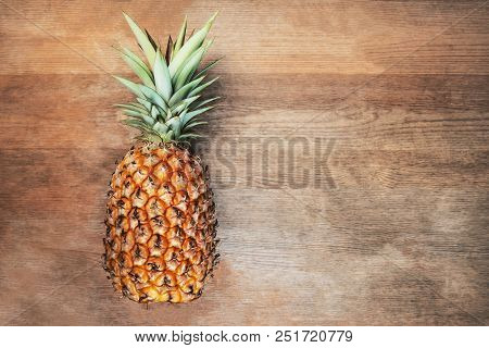 Single One Full Whole Organic Pineapple Fruit On Wooden Background Ripe Fully Grown Mature, Laid Dow