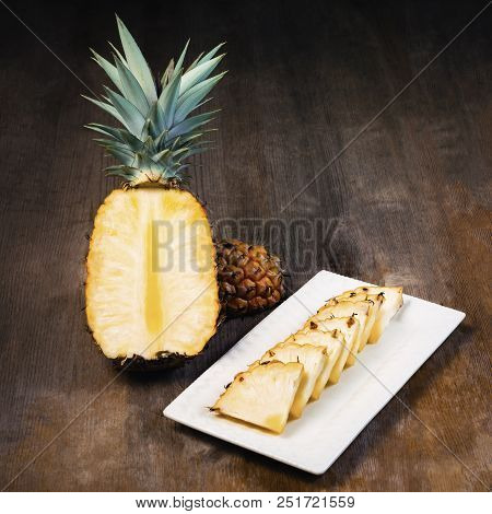 Pineapple Fruit Cut Half, Quarter And Wedges And  Displayed On White Plate And Wooden Background. Sq