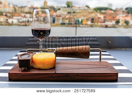 Glasses of port wine and a small wheel of cheese on the board at an outdoor restaurant with the Douro river and Dom Luis I bridge blurred in the background in Porto, Portugal