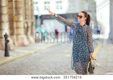 Happy Woman Walking In European Street. Young Girl Is Catching A Taxi In A Small Street In A Europea