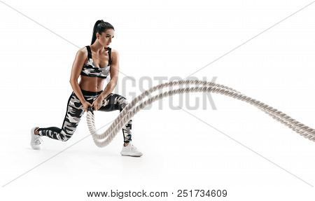Muscular Woman Working Out With Heavy Ropes. Photo Of Sporty Woman In Military Sportswear Isolated O