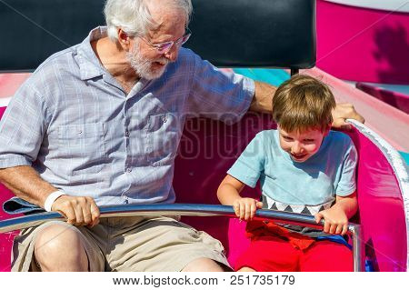 An Elderly Man And His Young Grandson Ride A Carnival Ride At A Theme Park.  The White Haired Man Lo