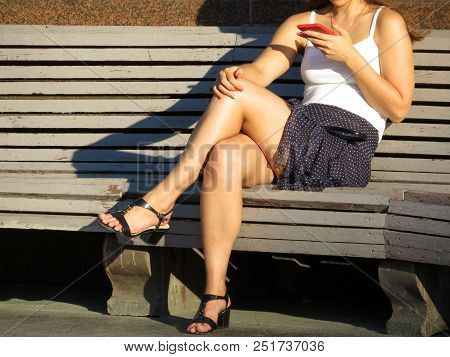 Woman In A Short Skirt And Black Sandals With High Heels Sitting With A Red Smartphone In Her Hand O