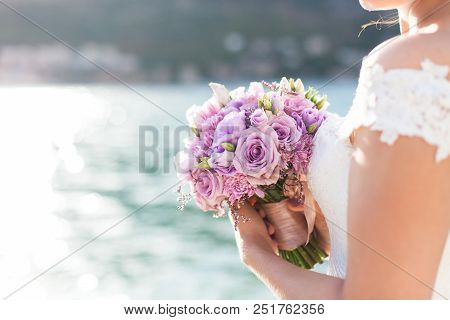 Bride Holds Wedding Bouquet From Lilac, Pink Flowers And Stands On Light Background Of Sea And Sunse