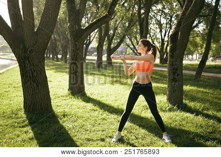 Attractive Young Caucasian Woman In Stylish Sports Outfit Doing Physical Exercises In Urban Park, St
