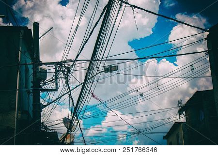 Electric And Tv Wires In A Favela With Blue Sky And Clouds Background.