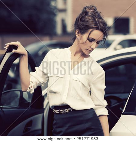 Young fashion business woman outside her car  Stylish female model with bun updo hair wearing white shirt and pencil skirt