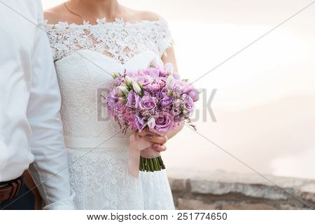 Bride And Groom Holding Hands And Wedding Bouquet From Lilac, Pink Flowers. Couple Were Married At W