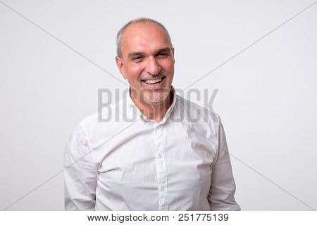 Confident Senior Man In White T-shirt Looking At Camera While Standing Against Gray Background. Self