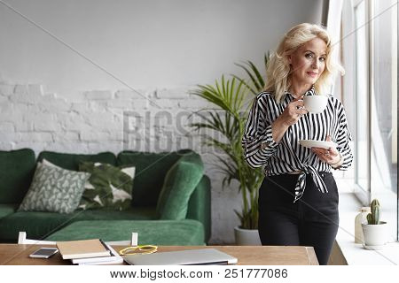 People, Lifestyle, Rest And Relaxation Concept. Indoor Portrait Of Gorgeous Successful Mature Woman