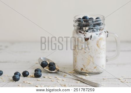 Overnight Oats With Whole Grain Cereal, Fresh Bluberries And Coconut Milk Served With A Spoon On Woo