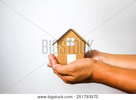 Brown House Model In 2 Human Hands On White Background. House Investment And Debt Concept.
